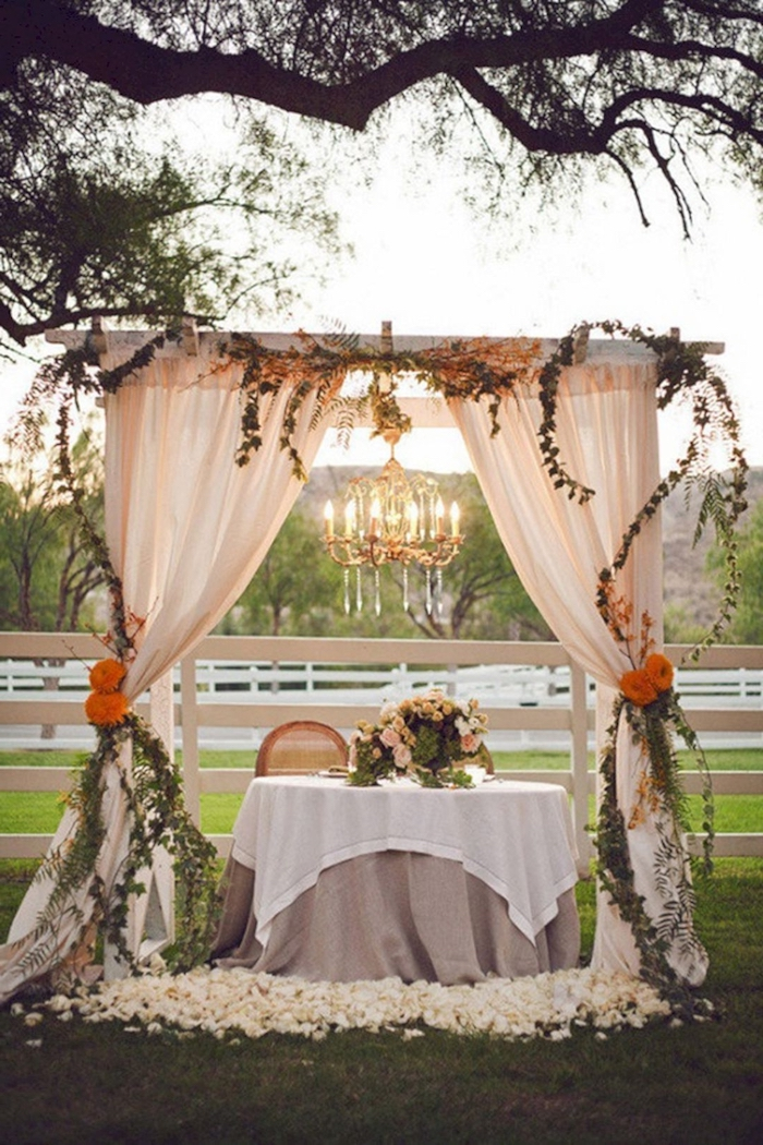 arch with flowers and blush tulle, pink roses flower arrangement on the table, wedding ideas for summer