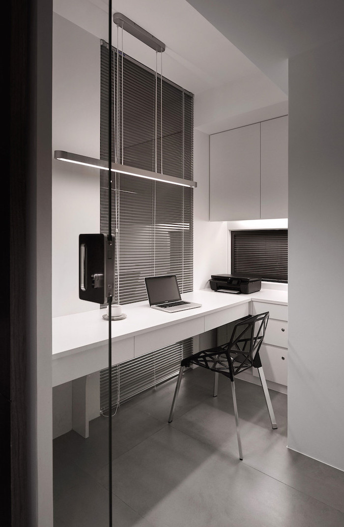 white wall cupboards and drawers, grey blinds, black geometrical chair, office pictures