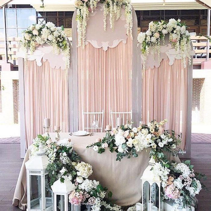 backdrop with blush tulle and hanging white flowers , white lanterns with flower arrangements, wedding ideas for summer