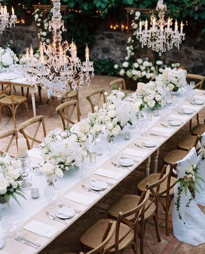 hanging candelabrum chandeliers, white roses flower bouquets on the table, candles on candlesticks, hanging decorations