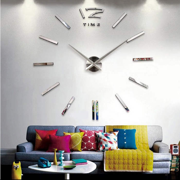 grey sofa, white wall with a large clock installation, wallpaper accent wall