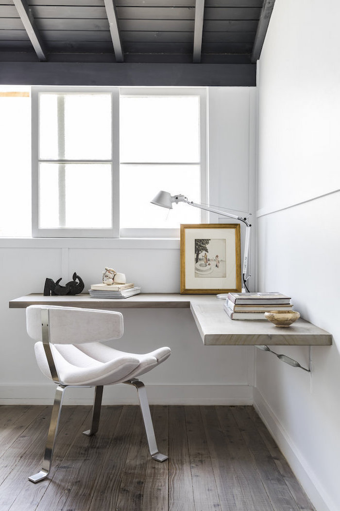 white walls, white velvet chair, office pictures, wooden desk with a desk lamp and books, wooden ceiling