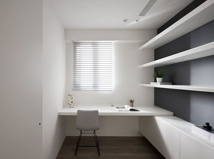 white bookshelves cabinets and desk, small grey chair, white blinds and walls, wooden floor, living room desk