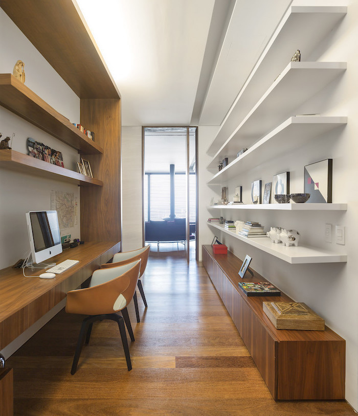 wooden and white bookshelves and cupboards, two orange chairs, office pictures, desktop computer