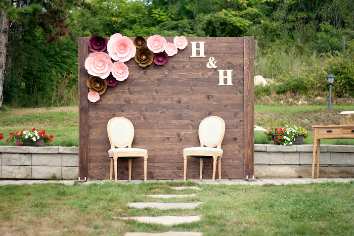 wooden backdrop with pink and brown flowers and initials, trees in the background, rustic wedding ideas