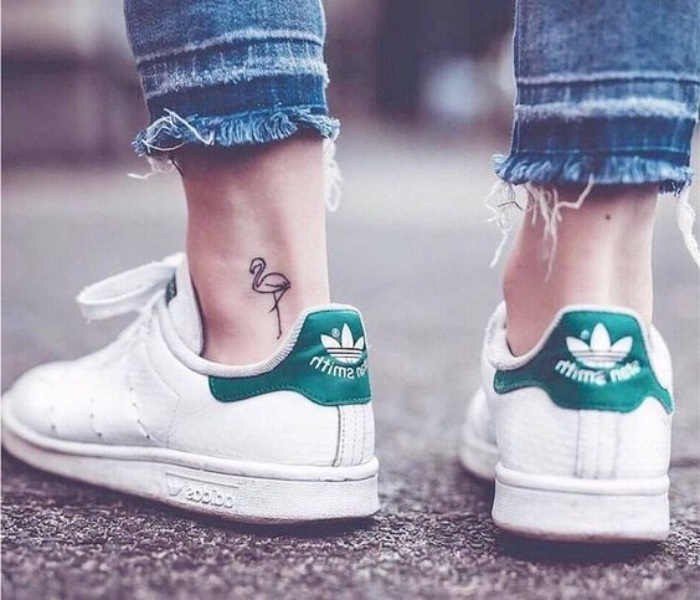 girl wearing white sneakers and jeans, small tattoo ideas, small flamingo ankle tattoo