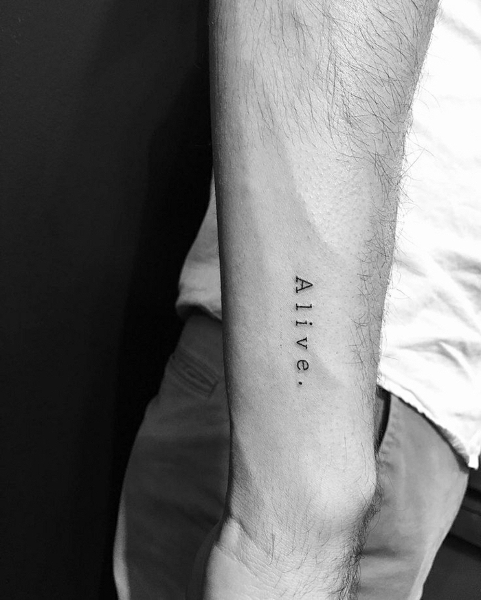 alive inscription, forearm tattoo, tattoos for men with meaning, white shirt, grey trousers, black background