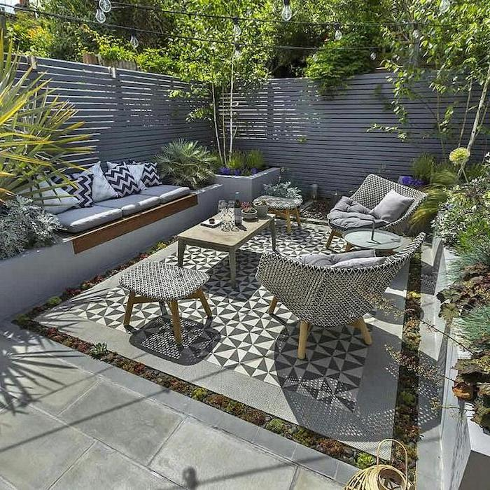 wooden garden furniture, small patio ideas, planted trees and bushes, cement tiles, wooden walls