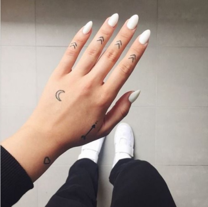 arrows moon and heart hand tattoos, small tattoos for men, woman wearing white nail polish, white sneakers