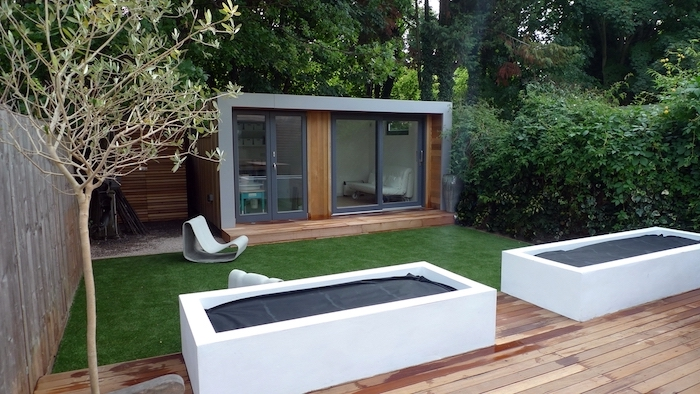 green grass small field, wooden shed, small patio ideas, planted trees, surrounded by tall hedges