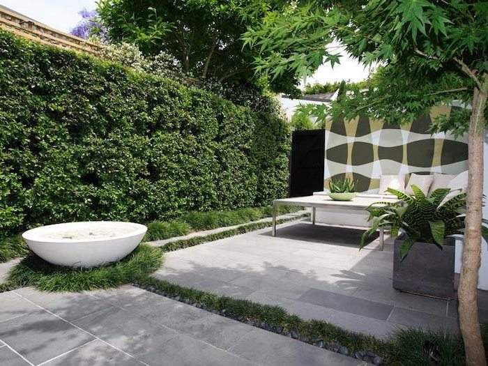 tall hedges, backyard garden ideas, small water fountain, potted plants, planted trees, garden furniture