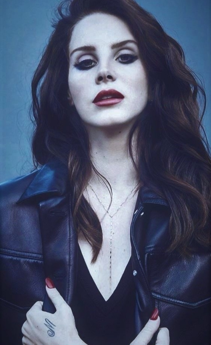 small tattoos, lana del rey looking at the camera, wearing black leather jacket, small m letter hand tattoo