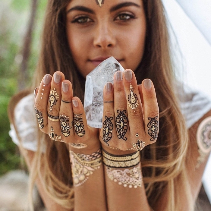 girl holding a crystal, black and gold henna tattoo, temporary tattoo, ring finger tattoos