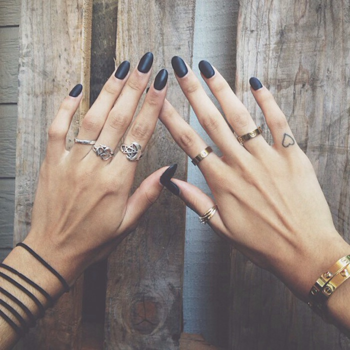 black almond shaped nails, many silver rings, small heart tattoo, finger tattoo ideas, wooden background