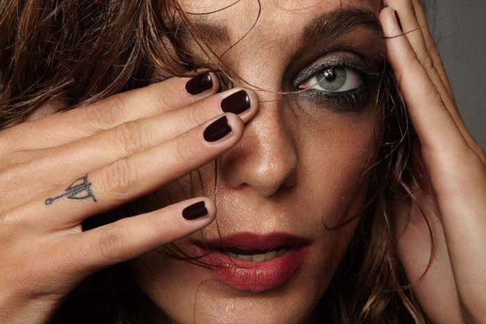 woman with flaking make up, small tattoo on her ring finger, finger tattoo, dark nail polish, green eyes