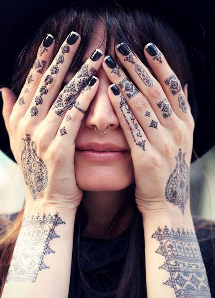 black nail polish, finger tattoo ideas, henna tattoos, many finger tattoos, woman covering her face
