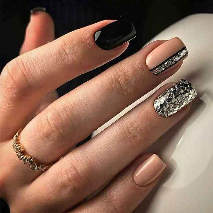black and nude nail polishes, silver glitter nail polish, nail art designs, golden ring on the middle finger