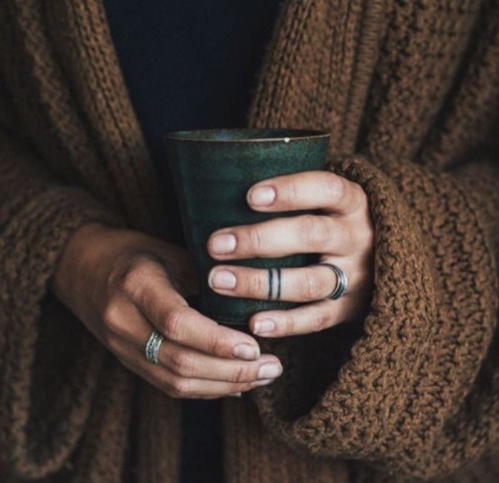 black rings tattoo around the finger. small tattoo, woman wearing a brown cardigan, holding a mug