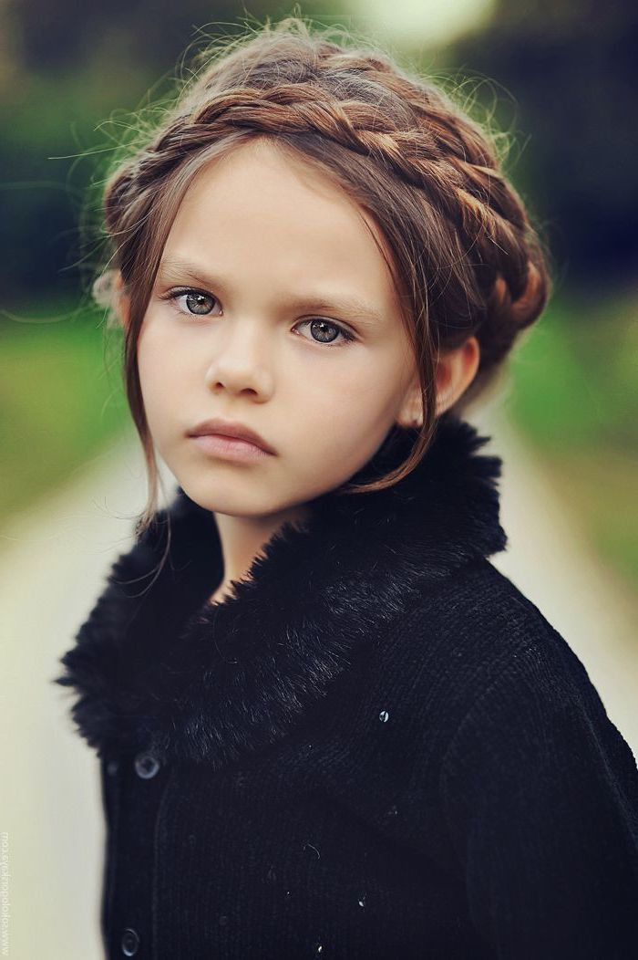 black fluffy cardigan, long brown braided hair, little girl hairstyles, green eyes, blurred background