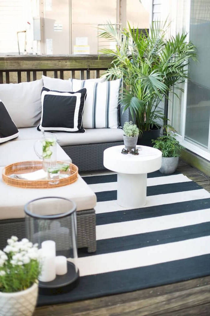 potted plants, next to a corner sofa, with throw pillows, backyard garden ideas, black and white striped rug