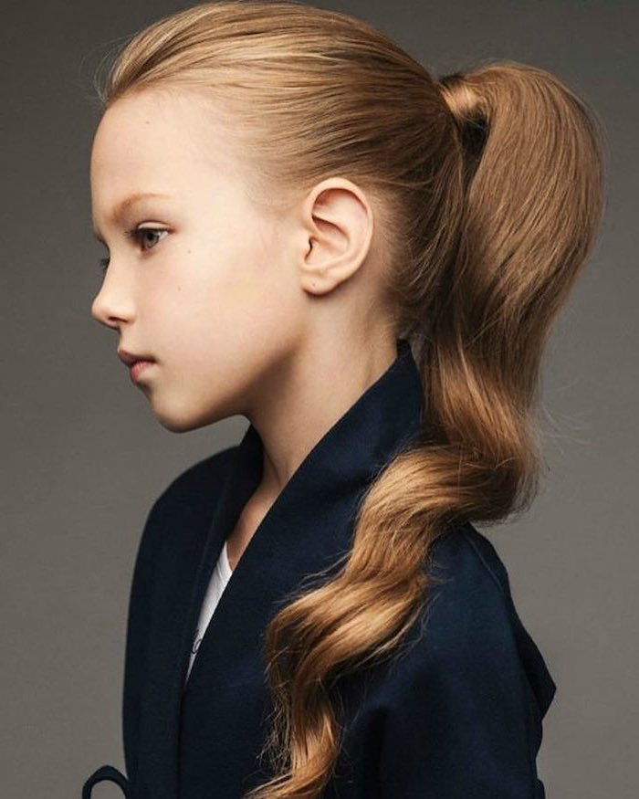 long wavy blonde hair, high ponytail, black blazer, grey background, little girl hairstyles