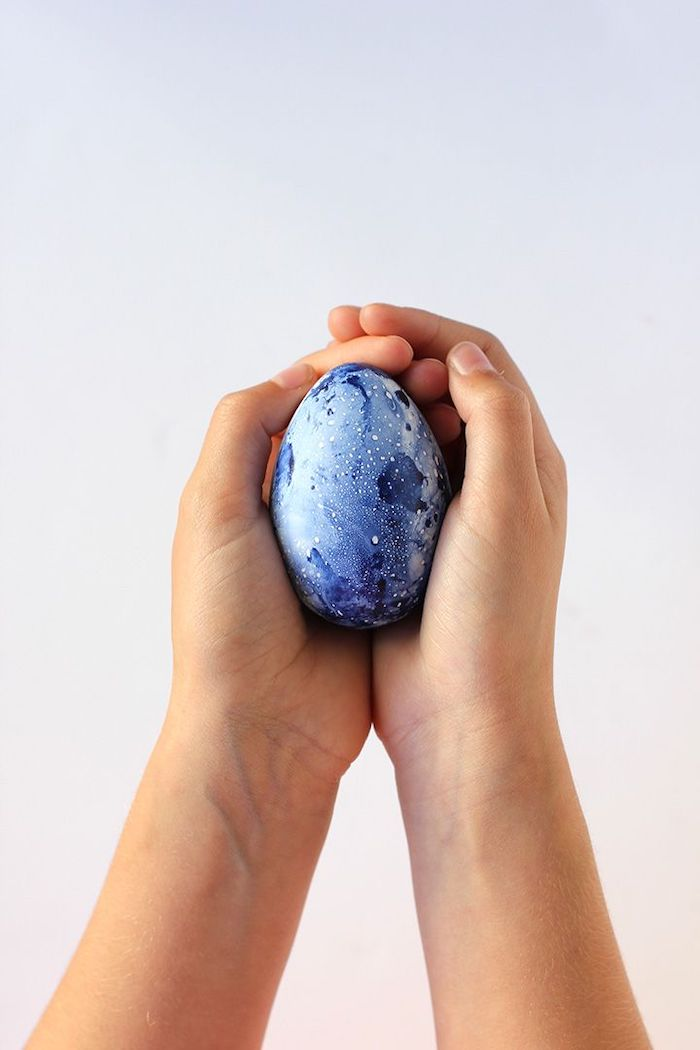 blue marble eggs, diy tutorial, easter egg designs, hands holding an egg, in front of a white background