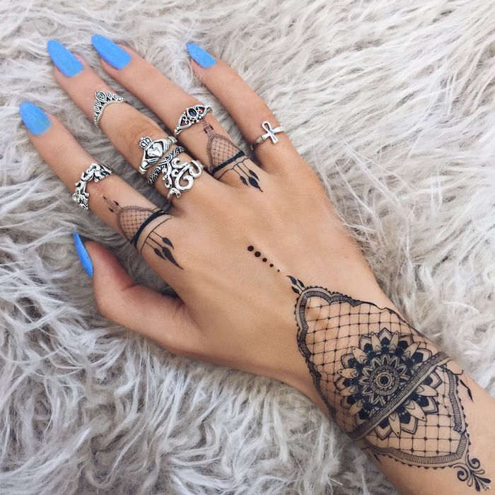 long blue nail polish, mandala tattoos, finger tattoo ideas, many silver rings, hand resting on a furry grey blanket