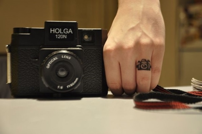 woman holding a vintage camera, small camera finger tattoo, small tattoos for women
