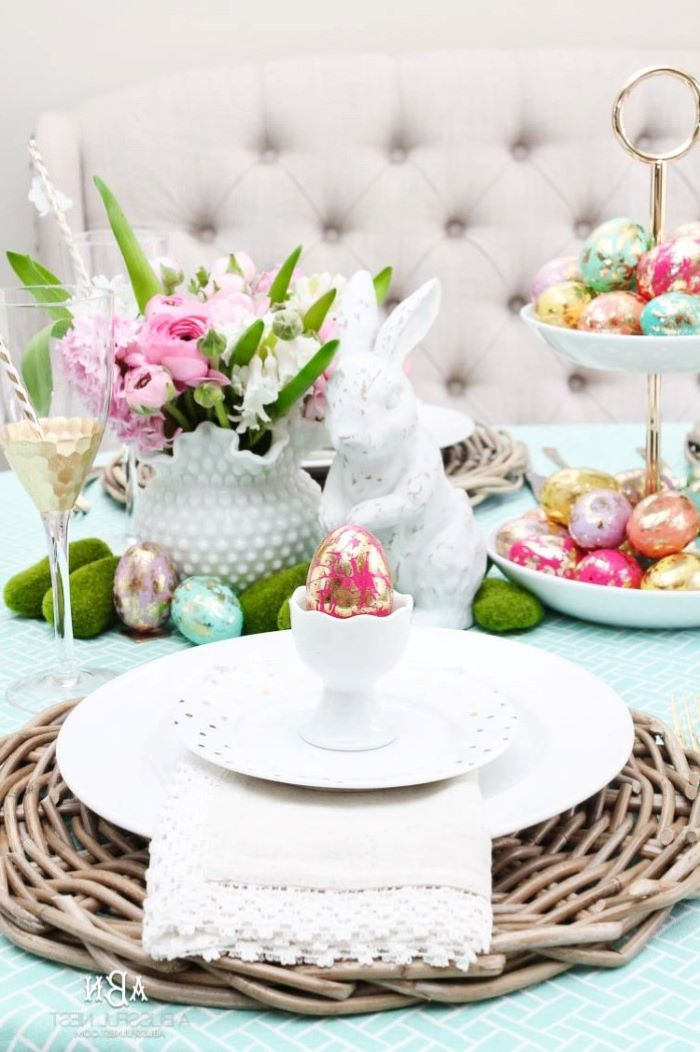 white plate settings, ceramic bunny figurine, dyed eggs on a cake stand, simple table decorations