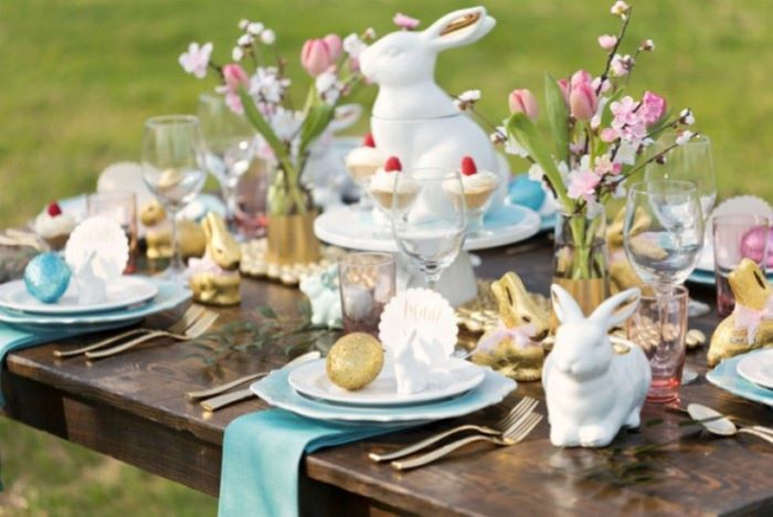 ceramic bunny figurines, simple table decorations, blue napkins, bouquets of flowers, dyed eggs