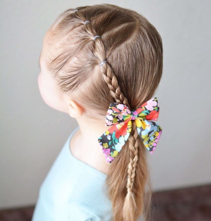 floral bow, long blonde hair in a ponytail and braid, blue shirt, short hairstyles for girls