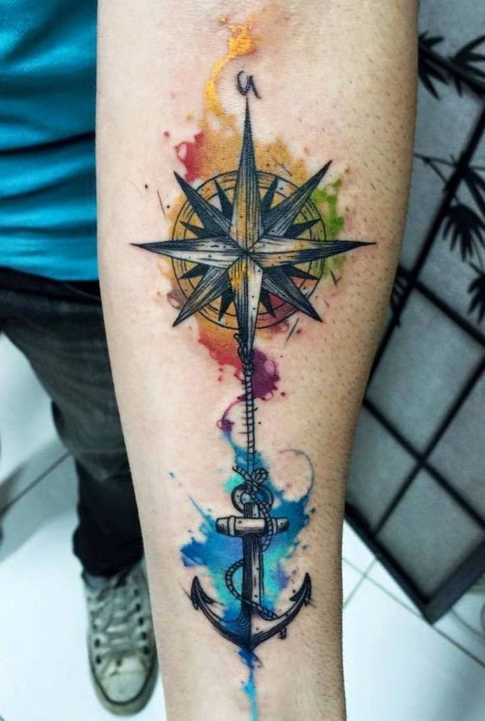 compass and anchor, watercolour forearm tattoo, tattoo ideas for men, man wearing blue shirt and jeans
