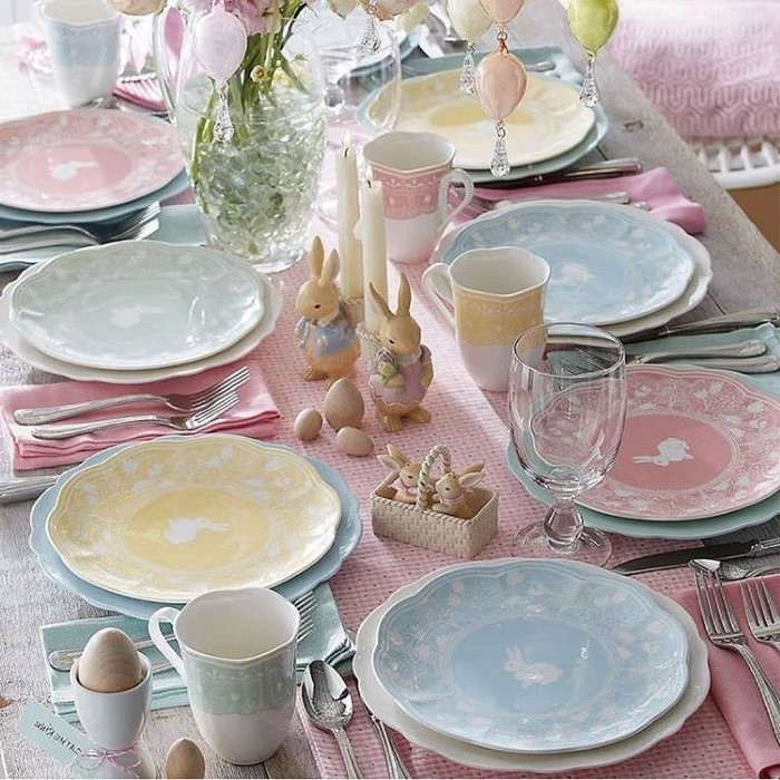 table settings with colourful plates, ceramic bunny figurines, easter table decorations