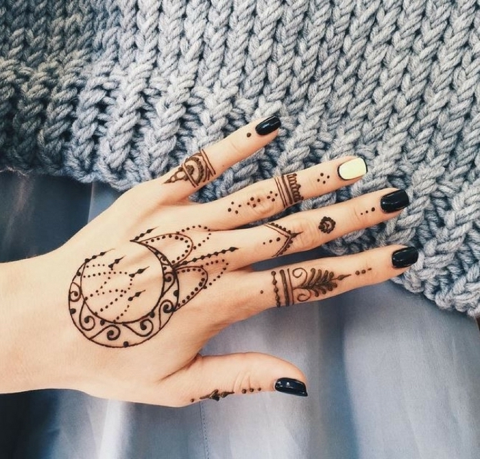 large henna tattoo, fingers crossed tattoo, hand resting on a grey blanket, with black nail polish