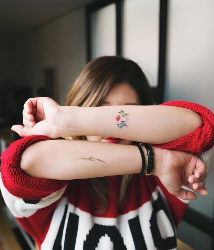 colourful flowers forearm tattoos, on both hands, small tattoos with meaning, woman wearing a red sweater