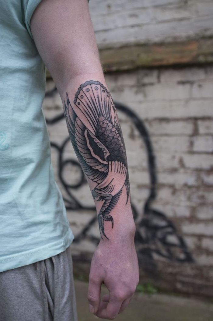 flying eagle, forearm tattoo, shoulder tattoos for men, man wearing a turquoise shirt, grey pants