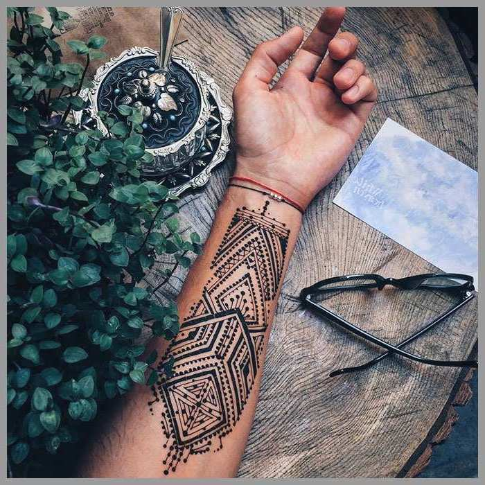 henna design, forearm tattoo, tattoo ideas for men, hand lying on a wooden table, next to glasses and potted plant