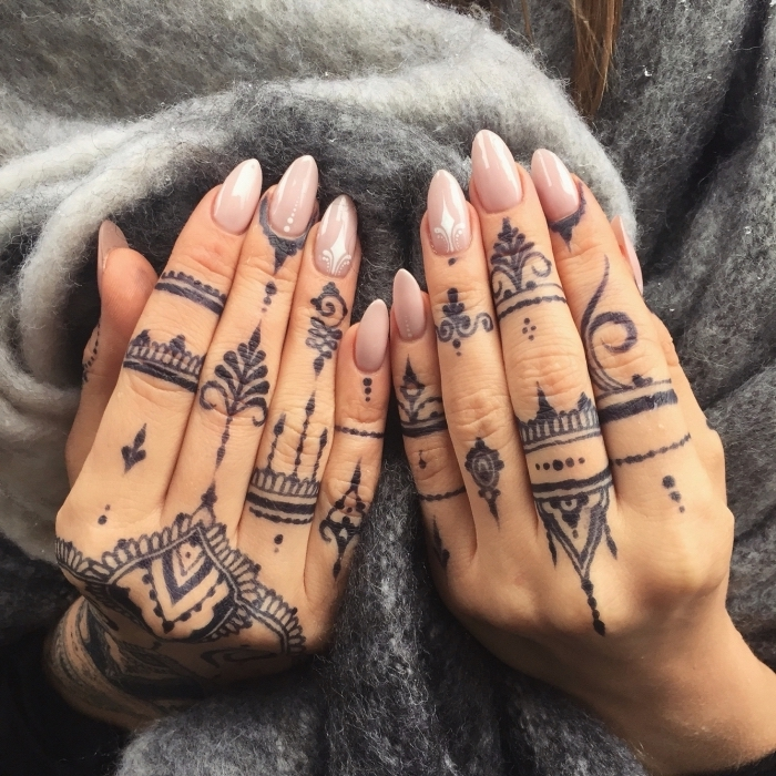 henna tattoos, hands resting on a grey scarf, with nude nail polish, small finger tattoos