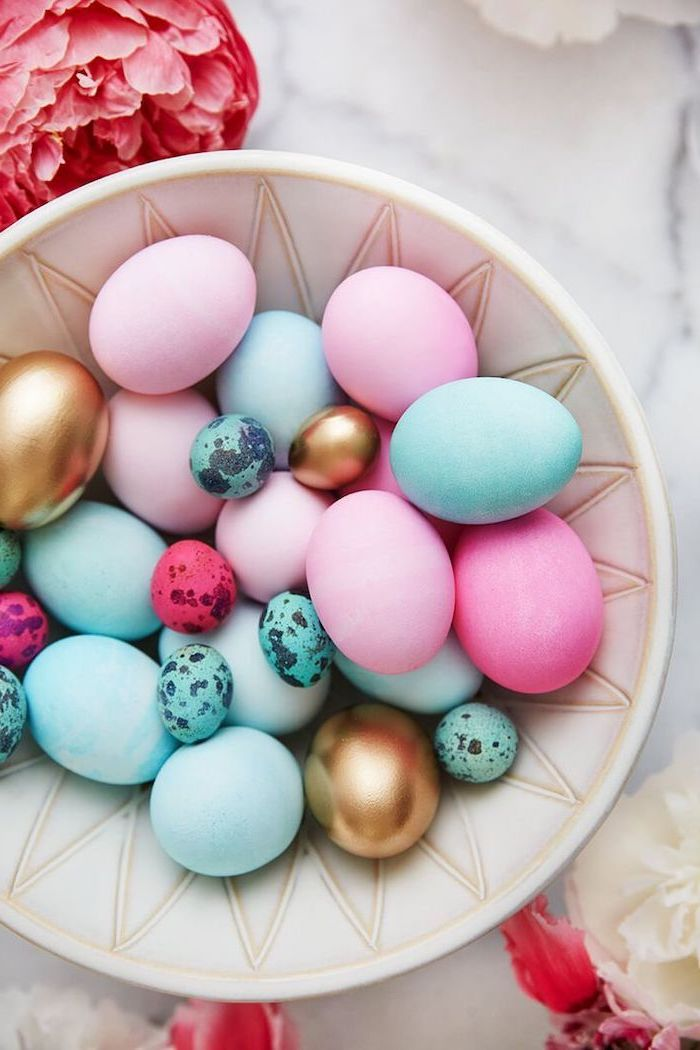 white bowl, full of colourful eggs, blue pink and gold, easter egg coloring ideas, flowers on the side