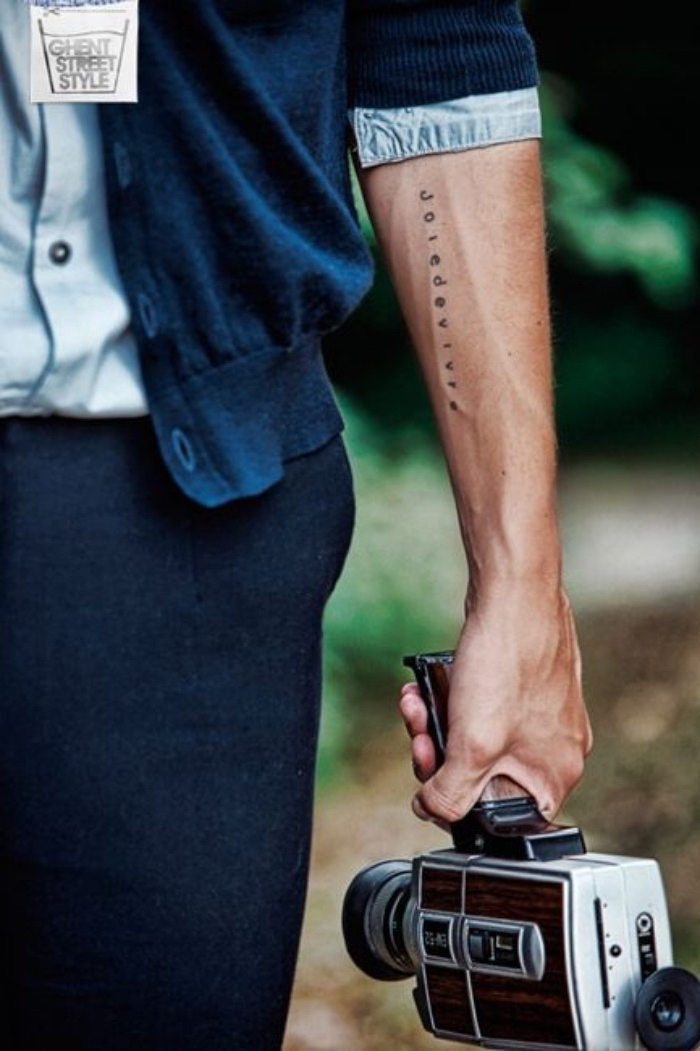 joie de vivre forearm tattoo, small bestfirend tattoos, man carrying a vintage camera, wearing a blue cardigan