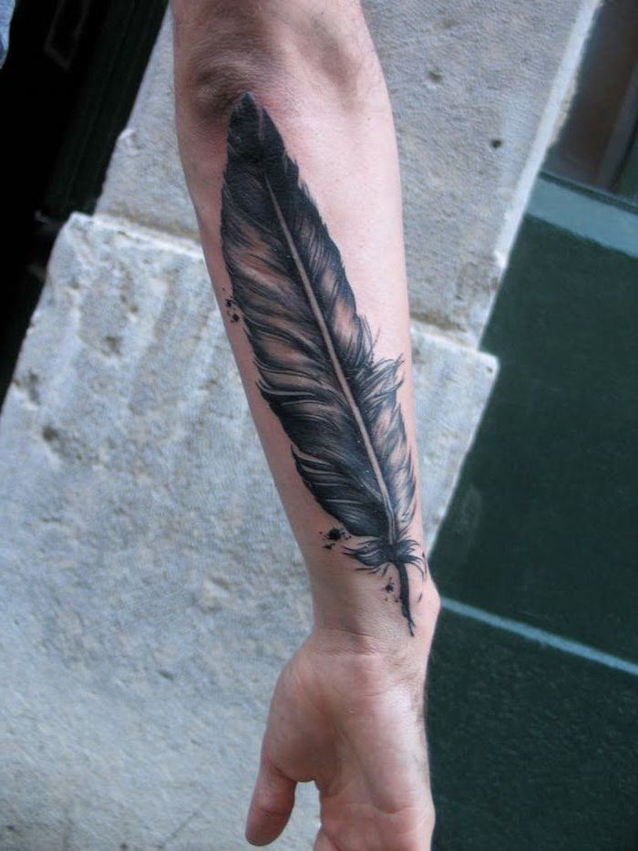 black and white feather, forearm tattoo, arm tattoos for men, cement blocks in the background