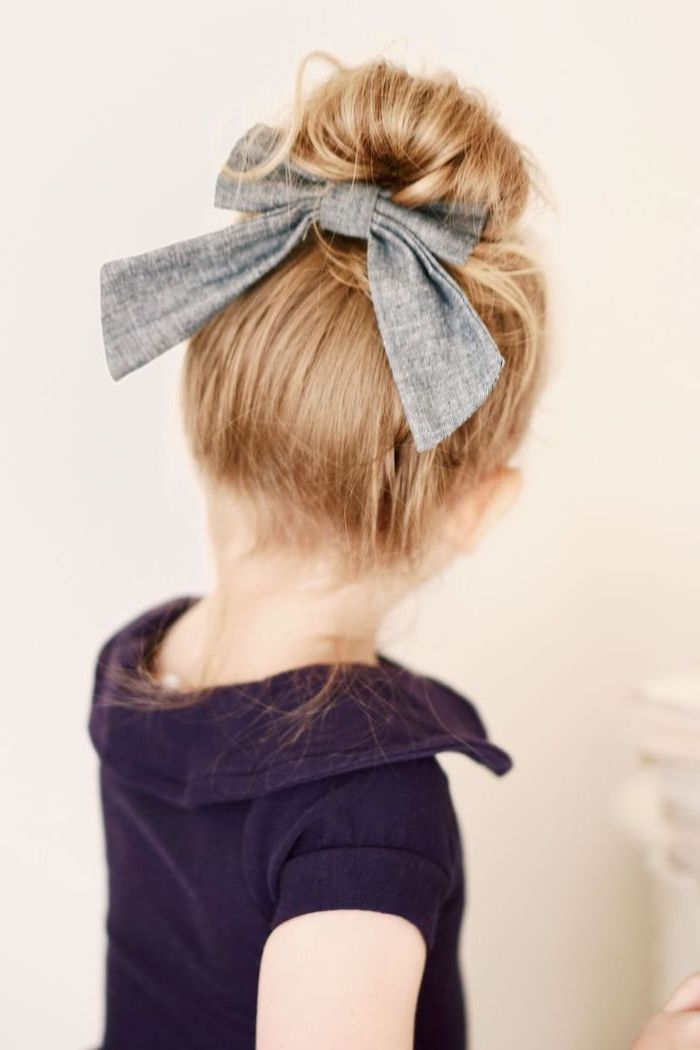 large grey bow, cute hairstyles for little girls, blonde hair in a messy bun, white background, purple top