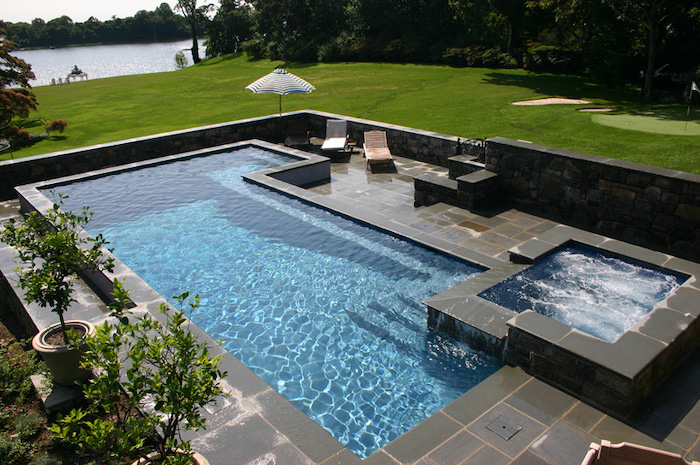 large pool, with a small hot tub, surrounded by black tiles, garden patio ideas, garden furniture