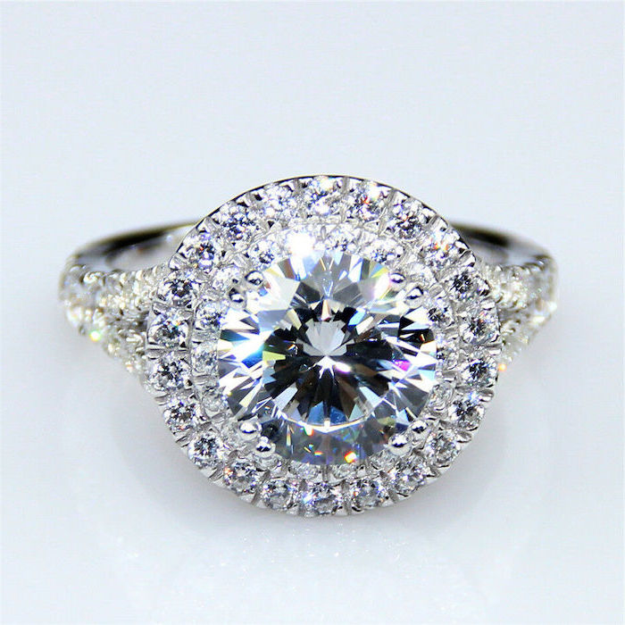 large round diamond, teardrop engagement ring, diamond studded band, white background