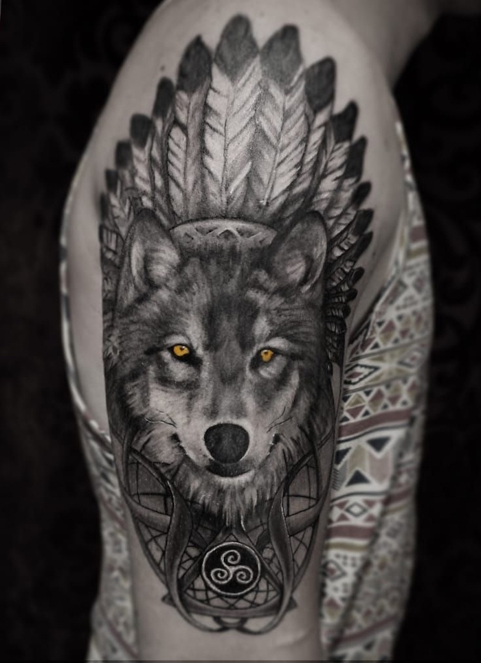 large wolf head, feathers on top, shoulder tattoo, forearm tattoos, man wearing a printed top