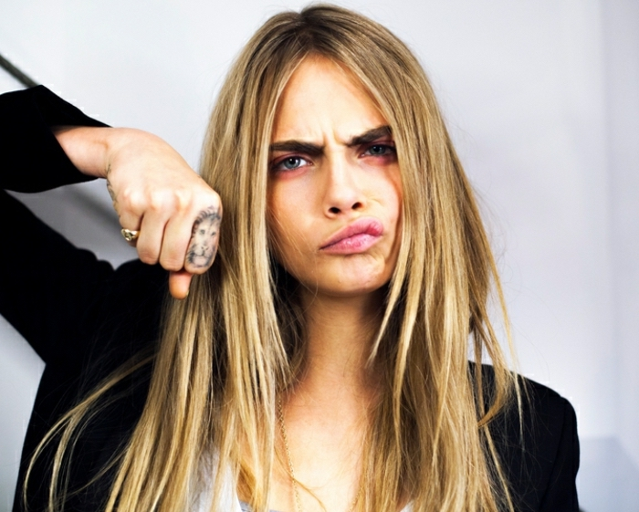cara delevingne with long blonde hair, lion tattoo, on the finger, finger tattoos for women, black blazer