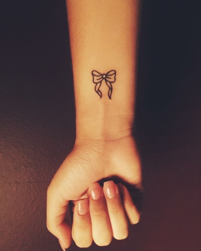 small bow wrist tattoo, small tattoo ideas for men, hand clutched in a fist, in front of a black background