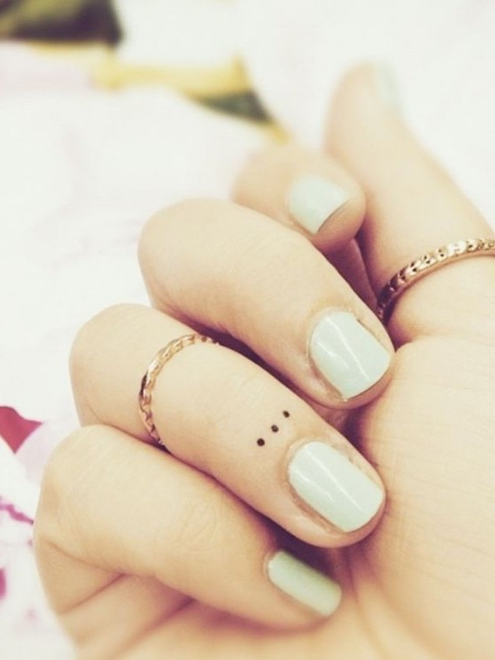three small dots under the nail tattoo, golden rings on two finger, small tattoo ideas for men, mint green nail polish