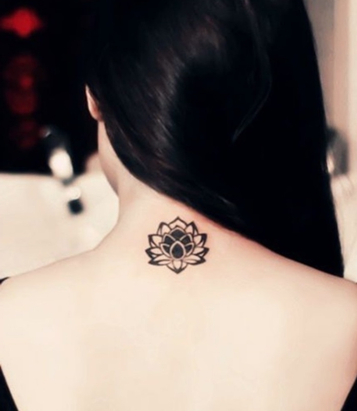 small lotus flower back tattoo, small tattoos for guys, woman with a long black hair, blurred background