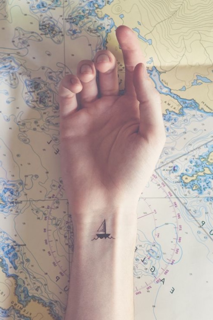 hand laying on a geographical map, small boat sailing wrist tattoo, small tattoo